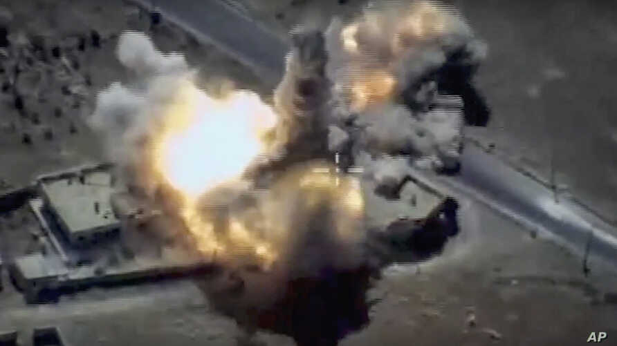 FILE - This image provided by Russian Defense Ministry Press Service and released June 23, 2017, shows a target in Syria hit by a missile launched by a Russian navy ship in the eastern Mediterranean. Russia's Defense Ministry said it fired cruise mis