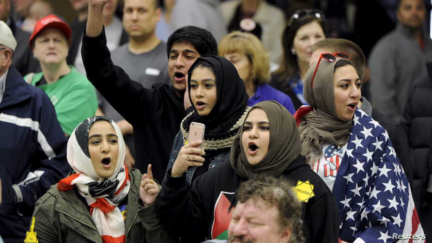 FILE - Young Muslims protest US Republican presidential candidate Donald Trump before being escorted out during a campaign rally in the Kansas Republican Caucus at the Century II Convention and Entertainment Center in Wichita, Kansas, March 5, 2016.