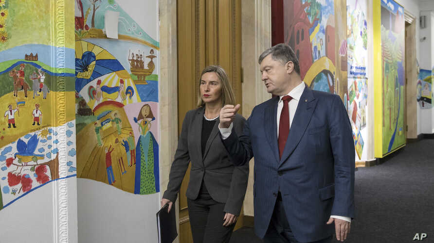 Ukrainian President Petro Poroshenko, right, and European Union foreign policy chief Federica Mogherini talk during a meeting n Presidential office in Kyiv, Ukraine, March 12, 2018.