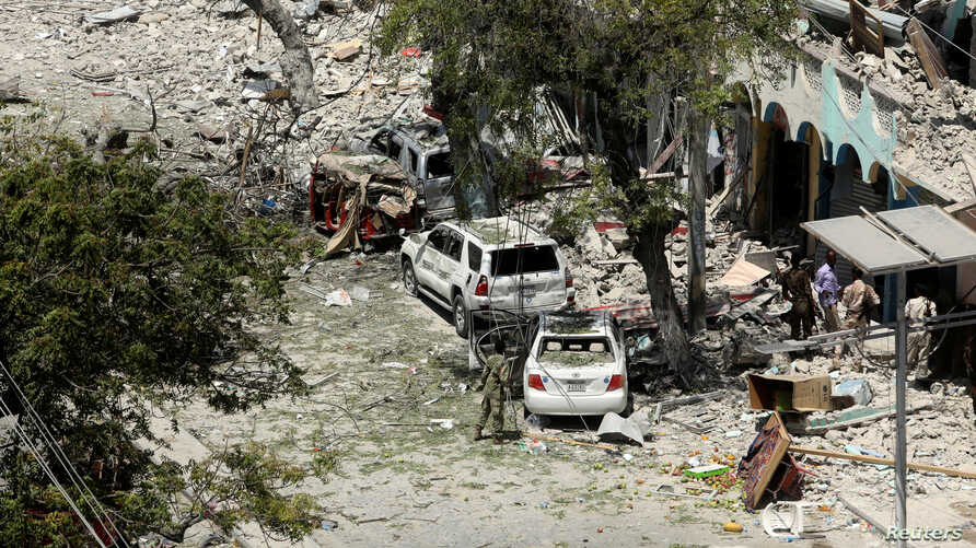 Security personnel are seen next to buildings damaged at the scene where a suicide car bomb exploded targeting a Mogadishu hotel in a business center in Maka Al-Mukaram street in Mogadishu, Somalia, March 1, 2019.