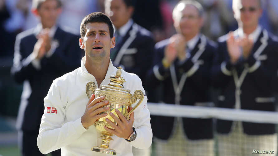Novak Djokovic of Serbia reacts while holding the winner's trophy after defeating Roger Federer of Switzerland in their men's singles finals tennis match on Centre Court at the Wimbledon Tennis Championships in London July 6, 2014.