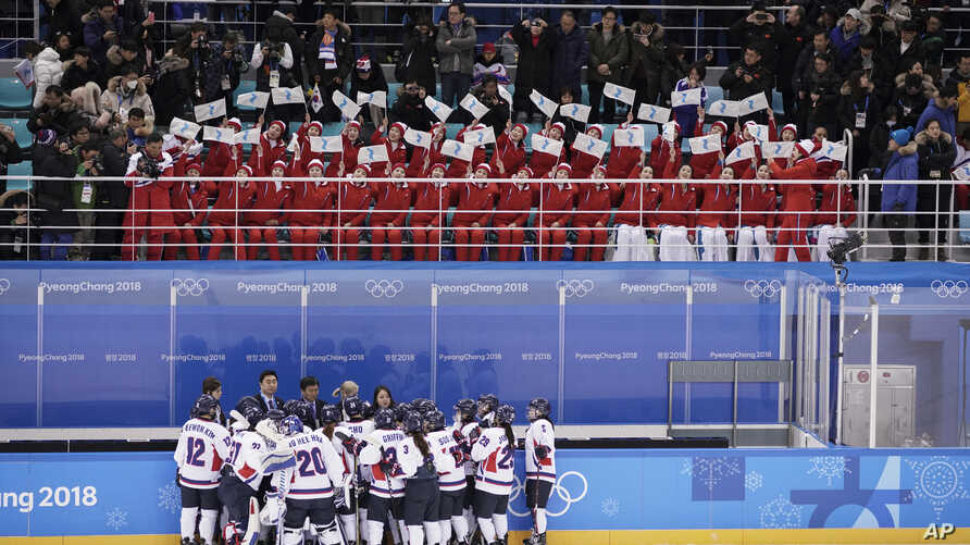 North Korea fans, top, wave the Korean unification flag as players of a combined Koreas team gather at the end of a women's hockey game against Switzerland, at the 2018 Winter Olympics in Gangneung, South Korea, Feb. 10, 2018.