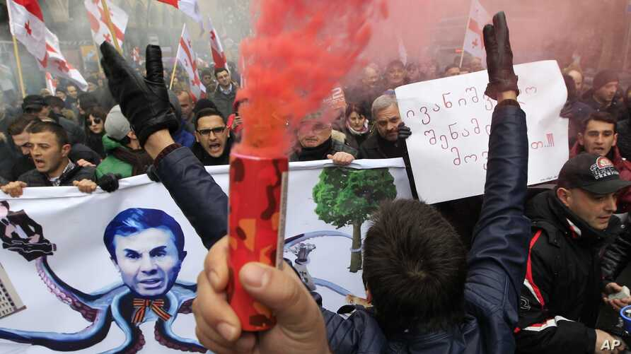 Protesters carry Georgian flags and a poster showing a caricature of former Prime Minister billionaire Bidzina Ivanishvili during a march in support of Rustavi 2 TV channel in Tbilisi, Georgia, Feb. 10, 2017.
