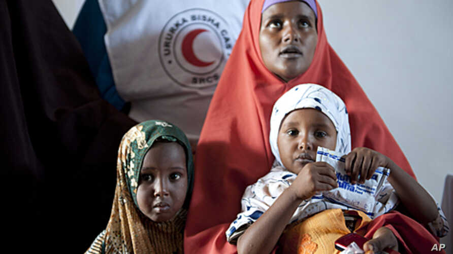 Hamdi Abdirgant sits with her children at a Red Crescent clinic in Harfo, Puntland, August 17, 2011.  Aid agencies estimate some 3.7 million Somalis are at risk of famine in the Horn of Africa country.