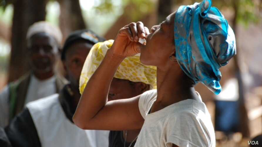 Woman drinking the first dose of the first oral vaccine against cholera in Africa during an epidemic, Guinea, Tougnifili/Mankountan, 2012.  Photo by David Di Lorenzo/MSF.