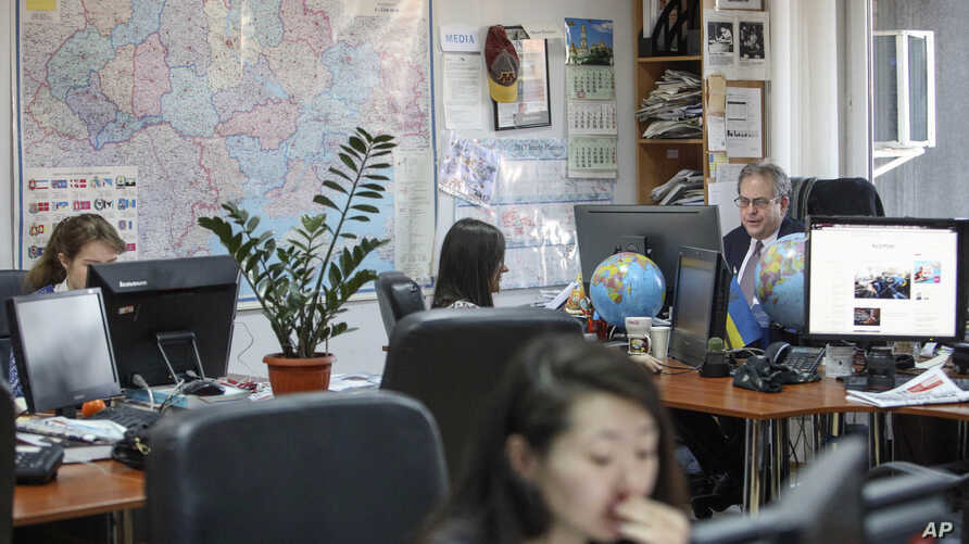 FILE - Kyiv Post chief editor Brian Bonner, right, and other journalists work at their desks in Kiev, Ukraine, Dec. 8, 2017.