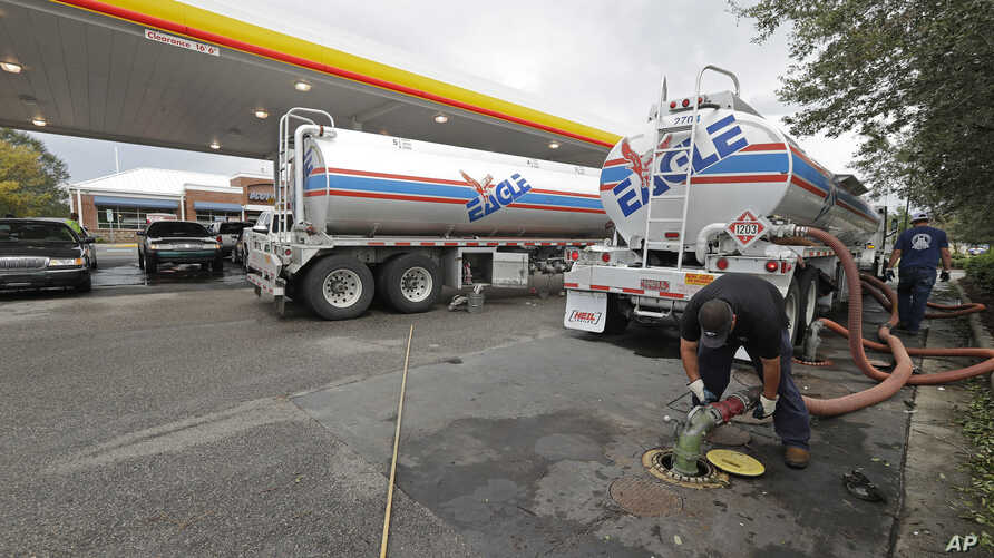 FILE - People wait in line as fuel is pumped from two tanker trucks at a convenience store in Wilmington, N.C., Sept. 17, 2018.