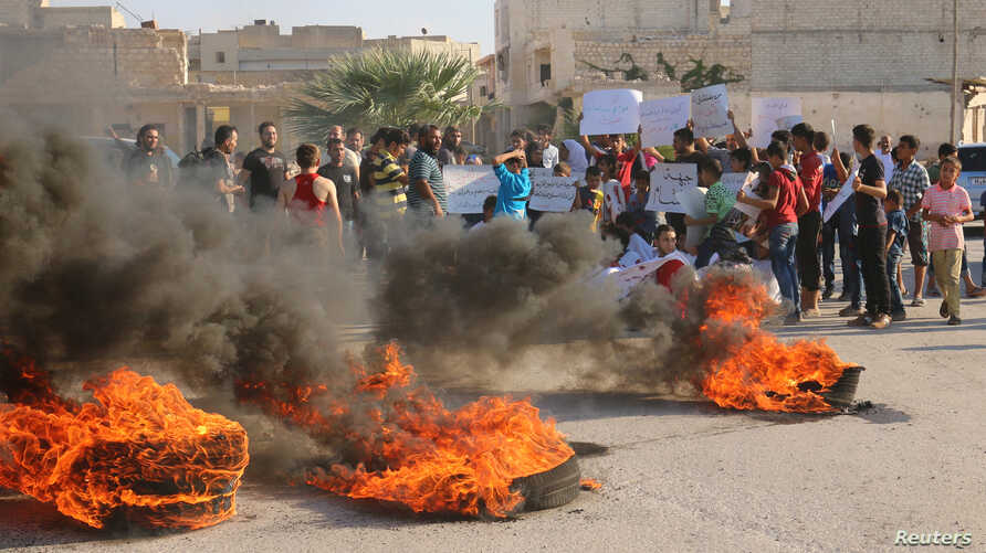 People gather near burning tires during a demonstration against forces loyal to Syria's president Bashar al-Assad and calling for aid to reach Aleppo near Castello road in Aleppo, Syria, Sept. 14, 2016.