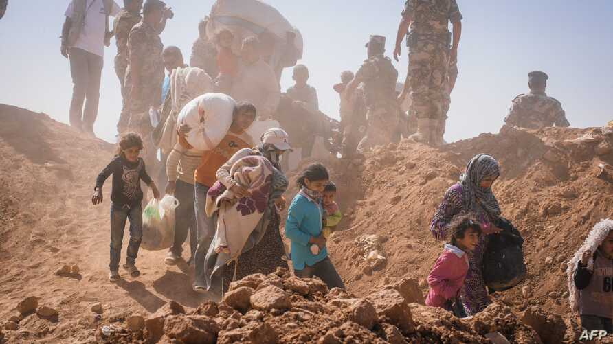 FILE - This handout picture taken on January 22, 2014 and released on August 29, 2014 by the United Nations High Commissioner for Refugees (UNHCR), shows Syrian refugees who stream across the border into Jordan at a remote border point in the east. (