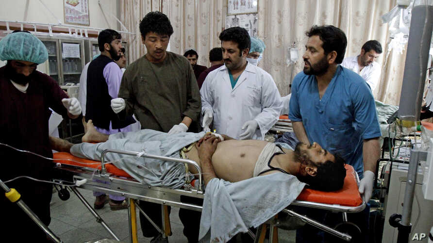 Afghan doctors and medics treat a wounded man at a hospital after a roadside bomb explosion in Kandahar, south of Kabul, April 7, 2014.