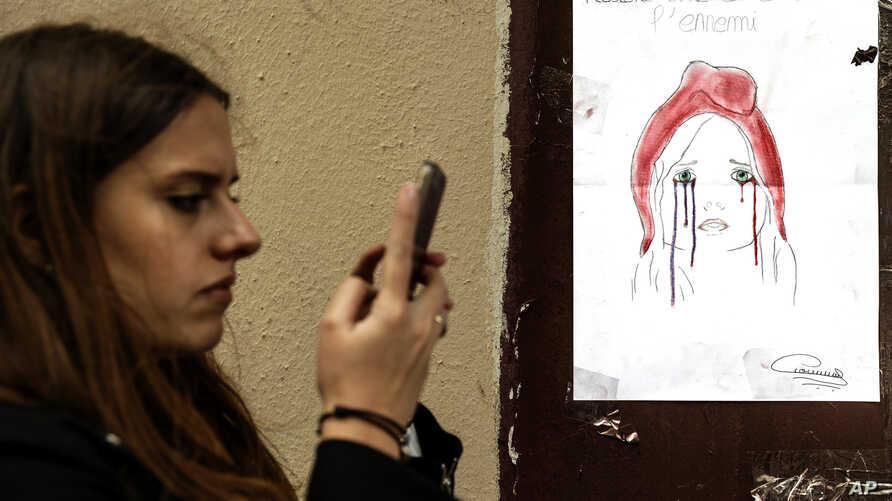 A woman checks her smartphone by a poster showing a weeping image of Marianne, symbol of the French Republic, near Le Carillon restaurant, a site of terrorist attacks, in Paris, Nov. 17, 2015. The attacks have triggered waves of social media communic