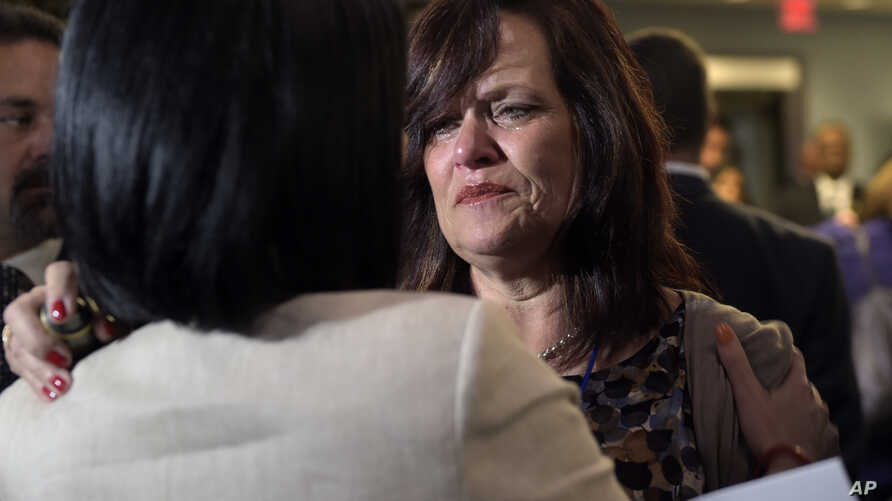 FILE - Sabine Durden (R), of Mineral Springs Ark., talks with Barbara Gonzalez, acting assistant director of Victims of Immigration Crime Engagement (VOICE) in Washington.