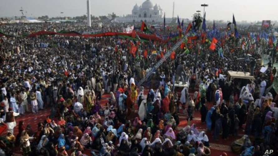 Thousands of supporters of Pakistan's former prime minister Benazir Bhutto take part in a rally to mark the fourth anniversary of her assassination at her tomb, seen in background, in Gari Khuda Bux near Larkana, Pakistan, December 27, 2011.