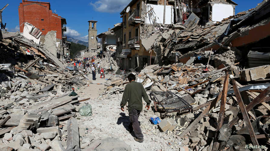 A man walks amidst rubble following an earthquake in Pescara del Tronto, central Italy, Aug. 24, 2016.