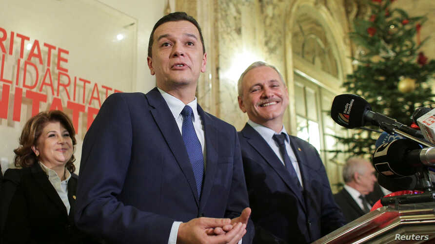 Sorin Grindeanu (C) gestures while answering a question during a press conference held alongside Romania's Social Democrat Party (PSD) leader, Liviu Dragnea (R), in Bucharest, Romania Dec. 28, 2016.