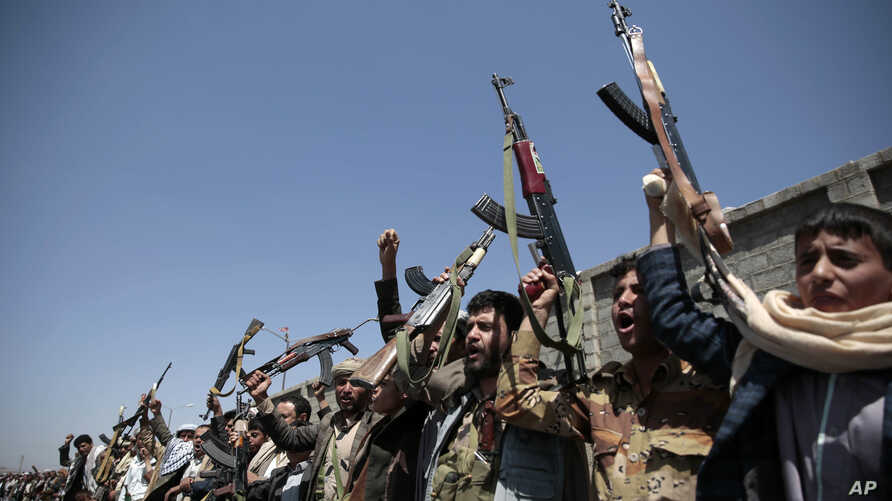 FILE - Tribesmen loyal to Houthi rebels hold their weapons and chant slogans during a gathering aimed at mobilizing more fighters into battlefronts in several Yemeni cities on October 2, 2016, in Sanaa, Yemen. The U.S. is weighing what military resp