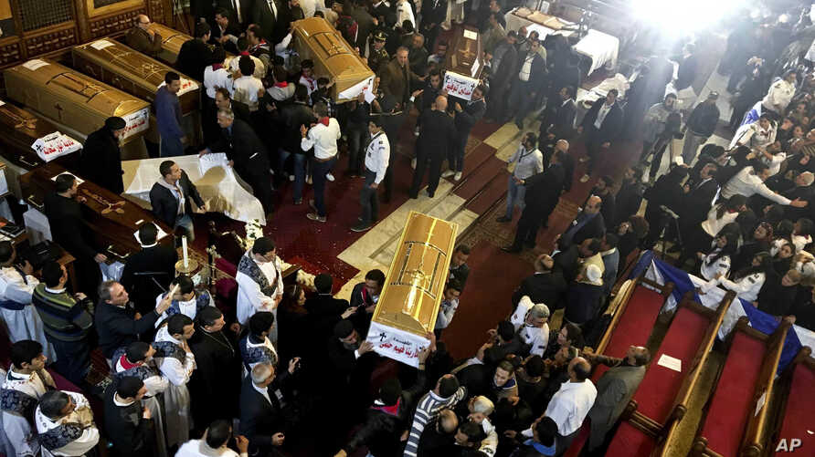 Coffins are taken into ambulances after a funeral service for victims of a Sunday cathedral bombing, at the Virgin Mary Church, in Cairo, Egypt, Dec. 12, 2016.