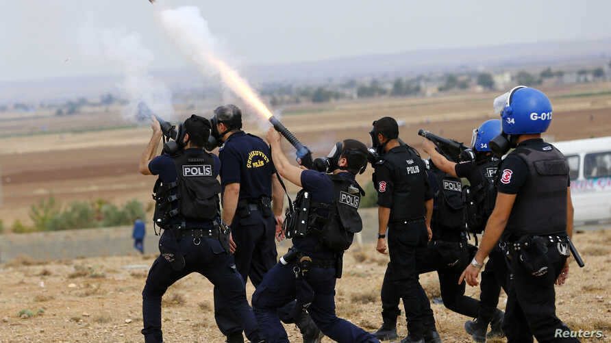Turkish riot police fire tear gas to disperse pro-Kurdish protesters near the Turkish-Syrian border in the southeastern town of Suruc in Sanliurfa province, Sept. 29, 2014.