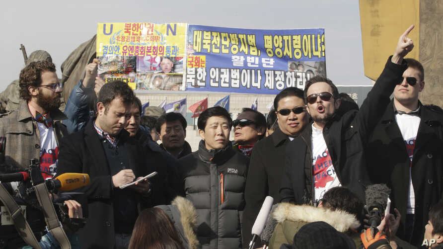 Thor Halvorssen, second right, the president of HRF, Human Rights Foundation, raises his arm and speaks during a press conference as Park Sang-hak, center, a North Korean Defector and the head of the Fighters for a Free North Korea, listens during a