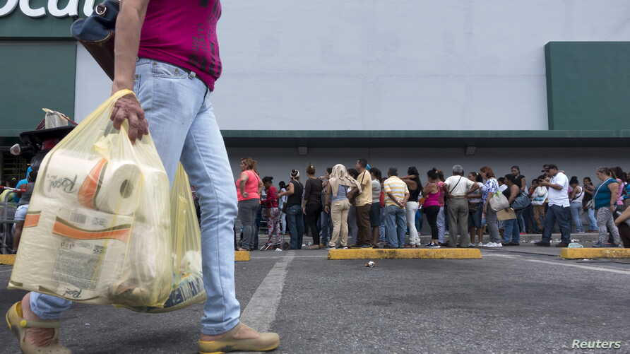 A woman carries bags with toilet paper rolls as people queue to buy staple items at a Makro supermarket in Caracas Aug. 4, 2015.