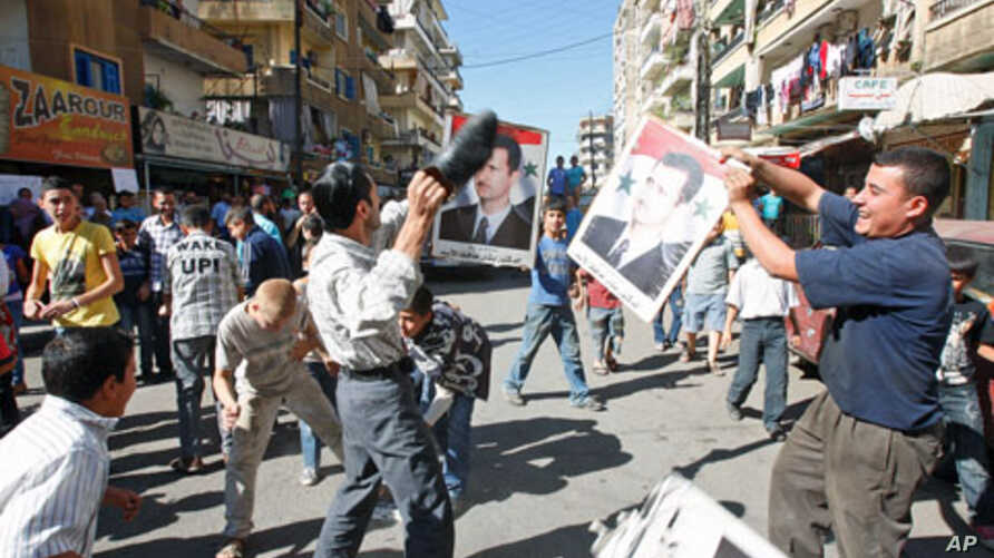 A protester uses a shoe to beat a picture of Syria's President Bashar al-Assad during a protest organized by Lebanese and Syrians living in Lebanon, in solidarity with Syria's anti-government protesters, in the port-city of Tripoli, northern Lebanon,