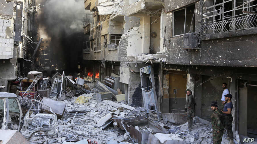 Syrian government forces walk down a destroyed street in the Hajar al-Aswad area on the southern outskirts of Damascus on May 21, 2018.