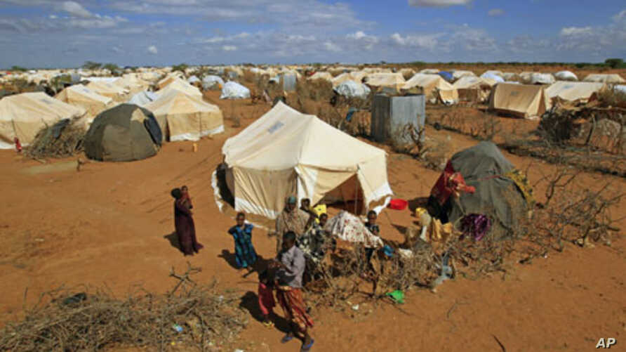 Refugees stand outside their tent at the Ifo Extension refugee camp in Dadaab, Kenya, October 19, 2011.
