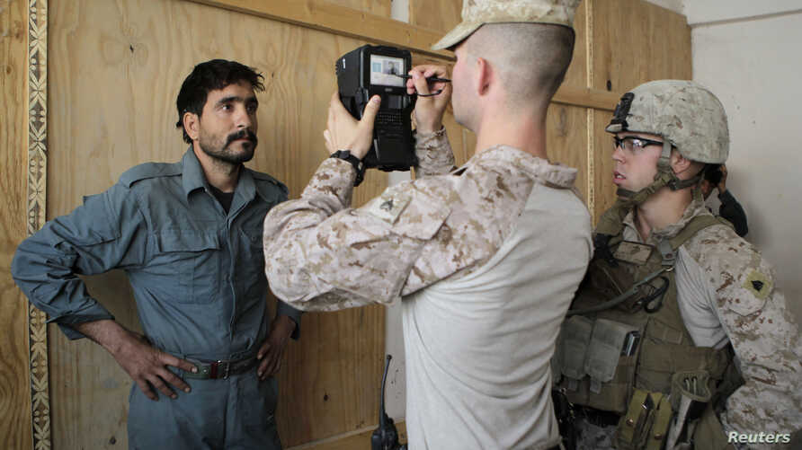 U.S. marines of Fox Co, 2nd Battalion, 7th Marines Regiment get a biometric scan of an Afghan local police trainee before the start of a basic police course training at Combat Outpost Musa Qal-Ah in Helmand province, southwestern Afghanistan, October