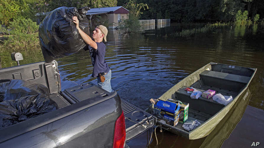 Daniel Stover, 17, loads personal belongings from a friend's home flooded home in Sorrento, La., Aug. 20, 2016.