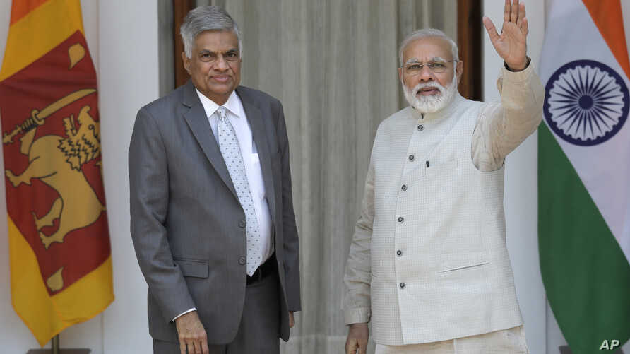 Indian Prime Minister Narendra Modi, right, waves to the media next to his Sri Lankan counterpart Ranil Wickremesinghe before their meeting in New Delhi, India, April 26, 2017.