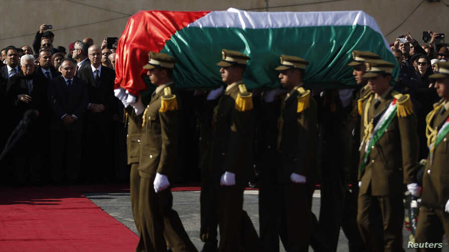 Palestinian President Mahmoud Abbas (back L) watches as Palestinian honor guards carry the coffin containing the body of Palestinian minister Ziad Abu Ein during his funeral in the West Bank city of Ramallah December 11, 2014. Thousands of mourners t...