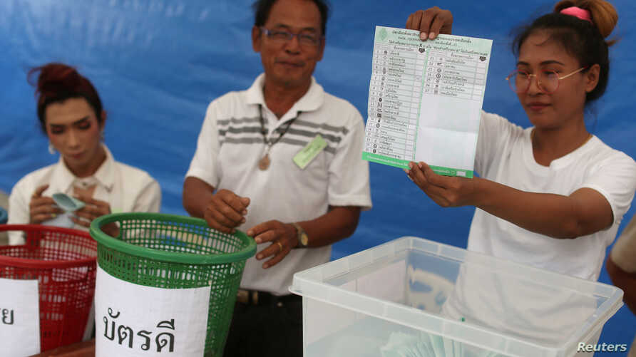 An electoral member shows a ballot during the vote counting, during the general election in Bangkok, Thailand, March 24, 2019.