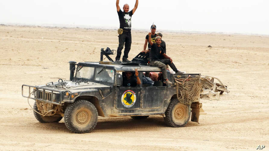 Iraqi soldiers flash victory signs after regaining control of the Ramadi Stadium and the neighboring al-Bugleeb area, Oct 6, 2015.