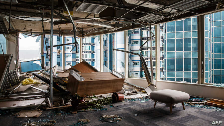Panels and debris from a collapsed ceiling are seen with blown over pieces of furniture in a company office, in a harbourside commercial building, whose windows were blown out the day before during Typhoon Mangkhut in Hong Kong on September 17, 2018.