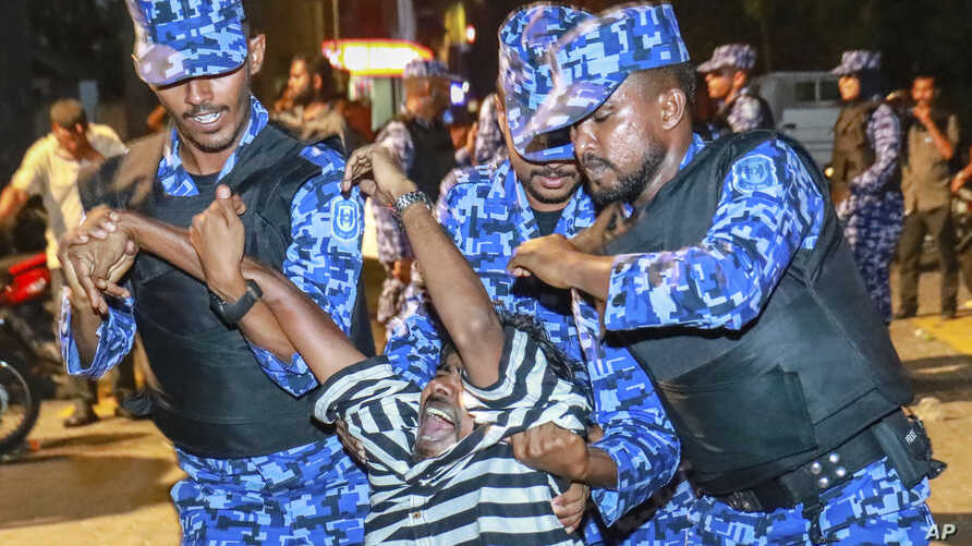 Maldivian police officers detain an opposition protester demanding the release of political prisoners during a protest in Male, Maldives, Feb. 2, 2018. Opponents of the Maldives government clashed with police on the streets of the capital Friday as