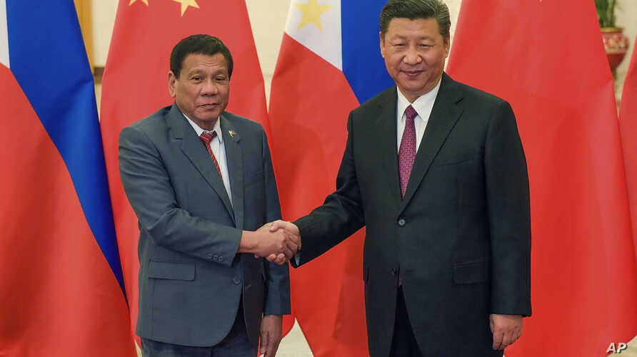 FILE - Philippine President Rodrigo Duterte, left, and Chinese President Xi Jinping pose for photographers on the sidelines of the Belt and Road Forum for International Cooperation at the Great Hall of the People in Beijing, May 15, 2017.