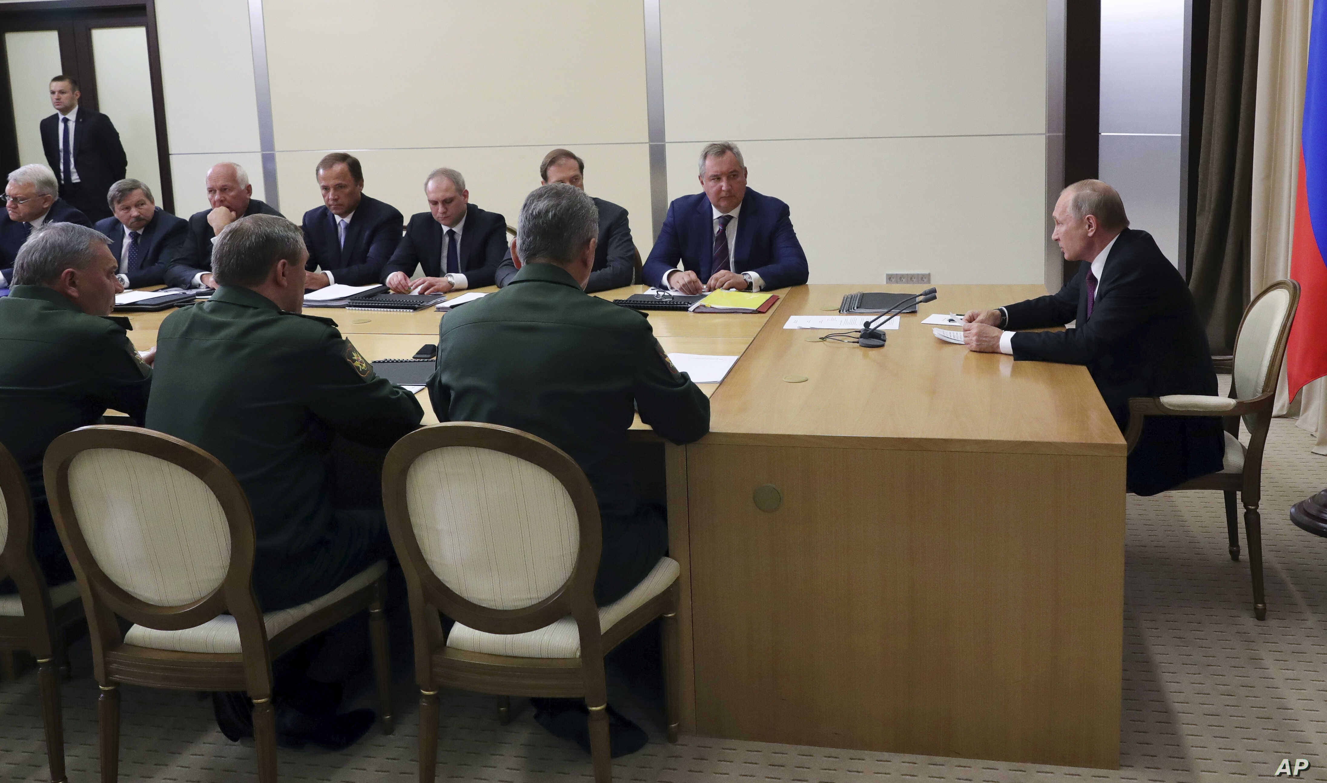 Russian President Vladimir Putin (R) chairs a meeting with the top military brass on military issues in Sochi, Russia, May 17, 2018.