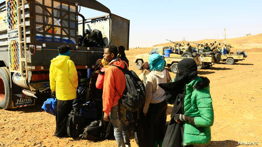 FILE - Illegal immigrants and traffickers who, according to the RSF, were caught while traveling in a remote desert area en route to Libya, gather to ride on a truck at Omdurman, Sudan, Jan. 8, 2017.