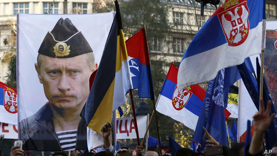FILE - A supporter of Serbian ultranationalist leader Vojislav Seselj holds a picture of Russian President Vladimir Putin during a protest In Belgrade, Serbia.