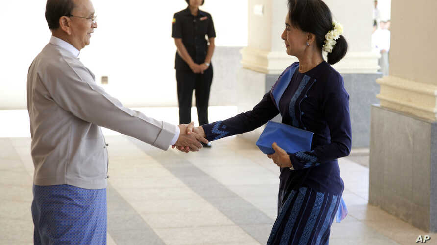 Myanmar President Thein Sein, left, shakes hands with Myanmar opposition leader Aung San Suu Kyi as they meet at Myanmar Presidential Palace in Naypyitaw, Myanmar, Oct 31, 2014.