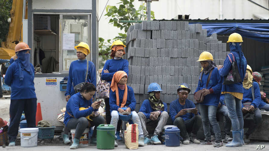 Cambodian migrant construction workers wait for their transport home outside a building site in downtown Bangkok, Thailand, Dec. 12, 2016. The International Labor Organization says in a report Tuesday that women make up almost 40 percent of migrant c...