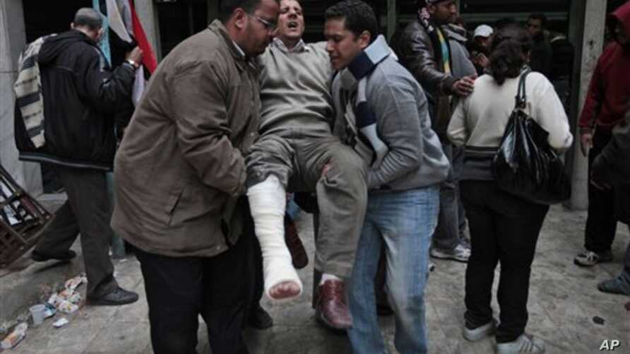 Anti-government demonstrators carry a man wounded during clashes with pro-government protesters, at a makeshift medical triage station, near Tahrir square, the center of anti-government demonstrations, in Cairo, Egypt, Wednesday, Feb. 2, 2011. Thousa