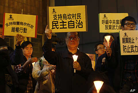"""A protester, center, holds up a placard reading: """"Supporting Wukan villagers, democracy autonomy"""" during a candlelight vigil outside the China Liaison Office in Hong Kong to support the Wukan villagers, December 20, 2011."""