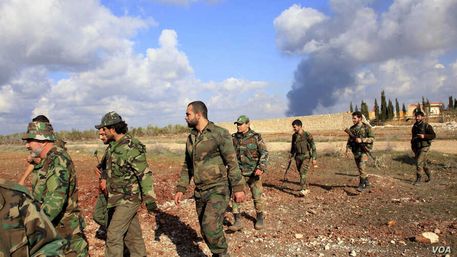 Forces loyal to Syria's President Bashar al-Assad walk in al-Mallah Farms, as fires burn alleged warehouses for the rebels in the background. Government troops said they regained control of the area north of Aleppo, Dec. 15, 2014.