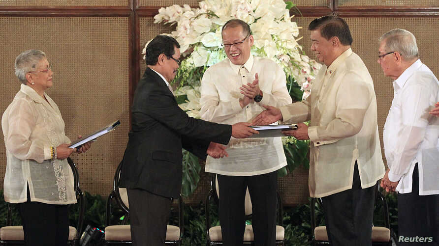 Philippine President Benigno Aquino (C) applauds as Moro Islamic Liberation Front (MILF) chief negotiator Mohagher Iqbal (2nd L) shakes hands with Senate President Franklin Drilon (2nd R) during the turnover ceremony of the draft Bangsamoro Basic Law...