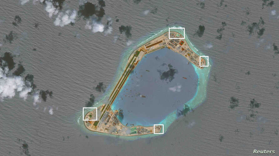 A satellite image shows what CSIS Asia Maritime Transparency Initiative says appears to be anti-aircraft guns and what are likely to be close-in weapons systems (CIWS) on the artificial island Subi Reef in the South China Sea in this image released o...