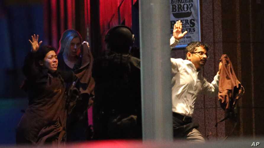 Freed hostages run toward armed tactical response police from a cafe under siege in downtown Sydney, Australia, Dec. 16, 2014.