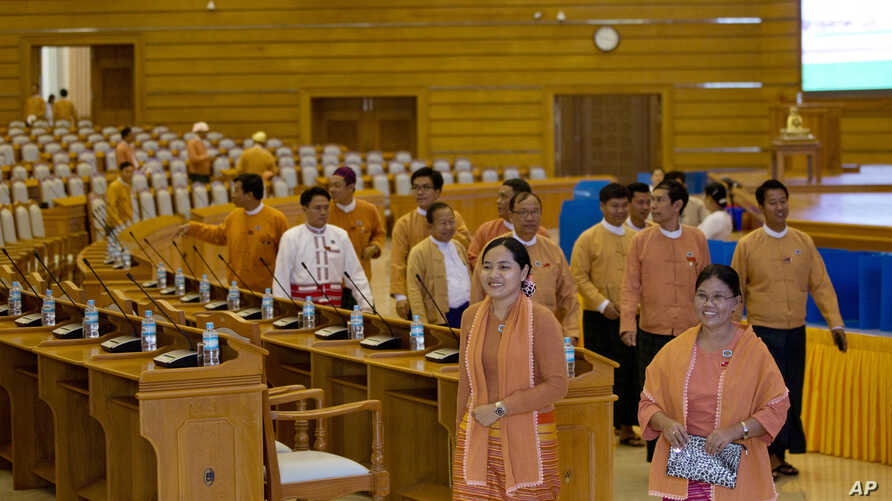 FILE - Lawmakers of National League for Democracy party (NLD) walk in parliament in Naypyitaw, Myanmar ahead of a parliamentary session, March 15, 2016.