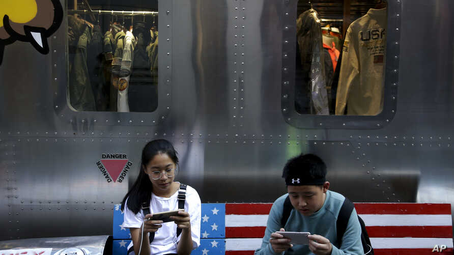 Shoppers sit on a bench with a decorated U.S. flag browsing their smartphones outside a fashion boutique selling U.S. brand clothing at the capital city's popular shopping mall in Beijing, Sept. 24, 2018.