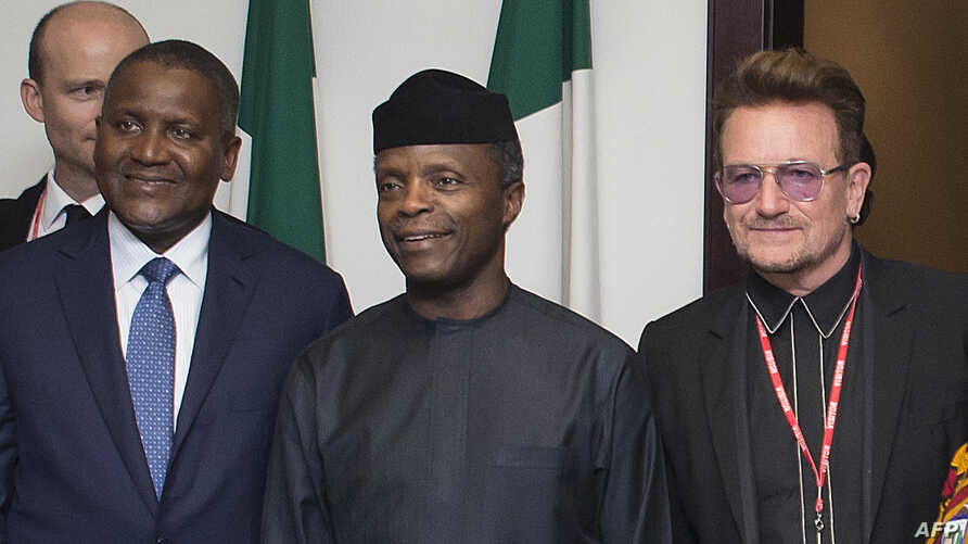Nigerian Vice President Yemi Osinbajo (C) flanked by Africa's richest man, Aliko Dangote, (L) and international rock star, Bono, meet in Abuja, Aug. 29, 2016.